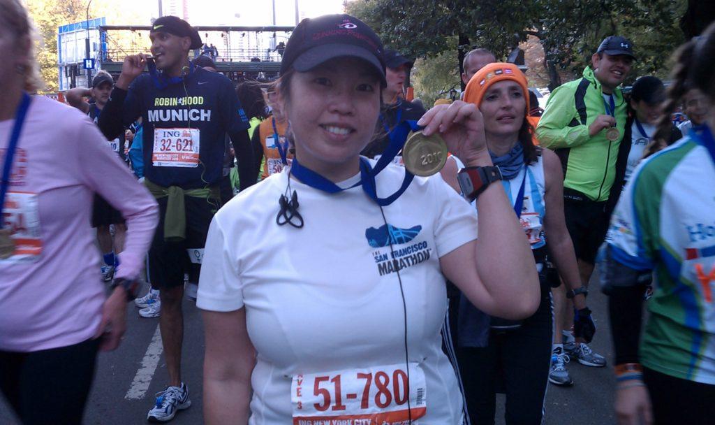NYC marathon runner holding her medal